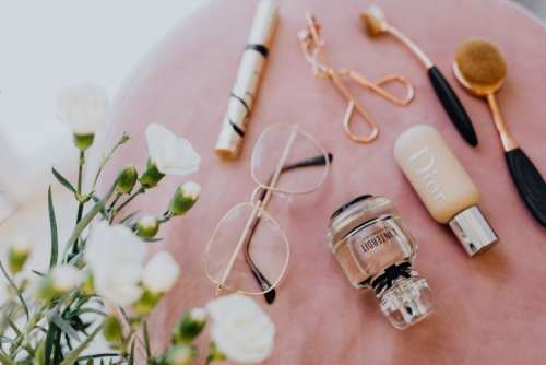 Makeup brushes, eyelash curler & a bottle of perfume on pink velvet