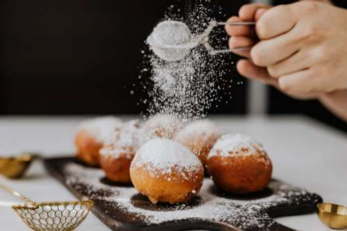 Homemade doughnuts covered with powdered sugar. Fat Thursday in Poland.
