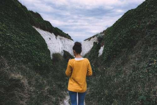Woman in Yellow Mustard Sweater Between Hills