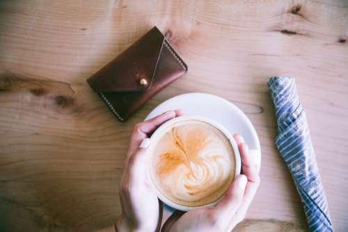 cappuccino hands table purse money