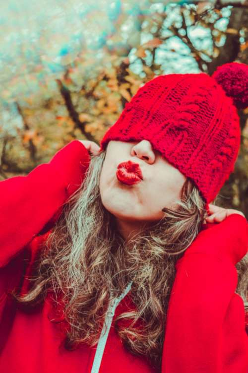 woman red hat kiss nature