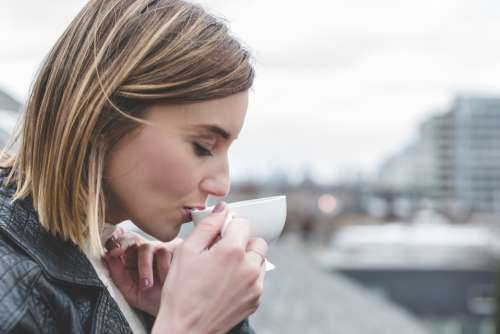 woman sipping tea outside person