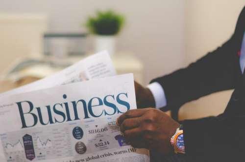 business newspaper reading stock market watch