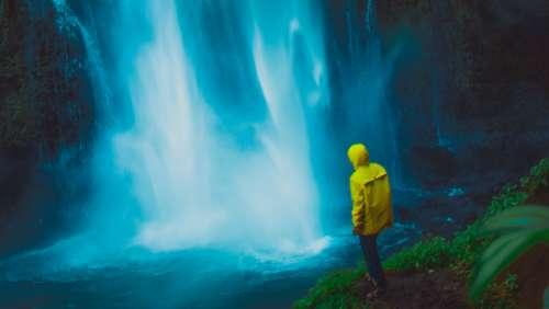 dramatic waterfall mist man yellow