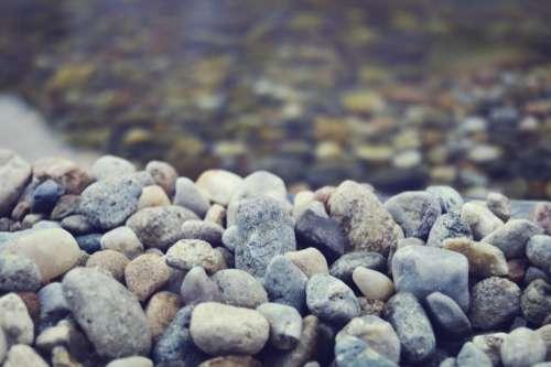 rocks pebbles beach clear water blue filter