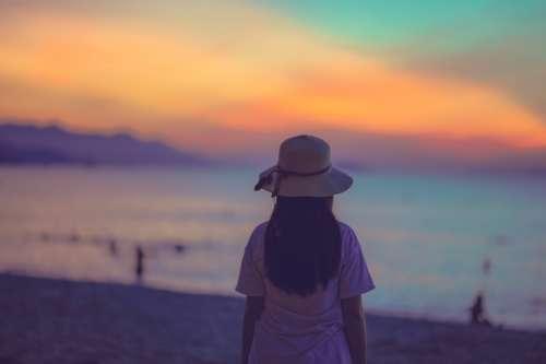 woman backlit beach clouds sky