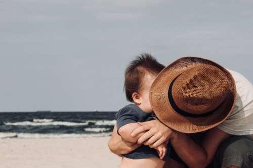 father son beach hat sea