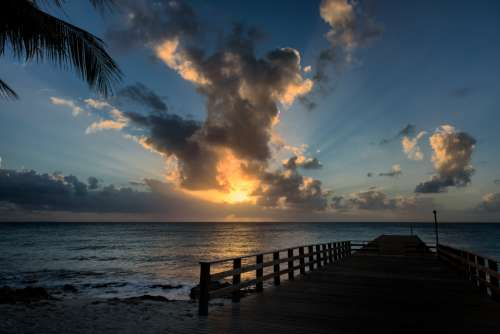 tropical pier sunset water ocean