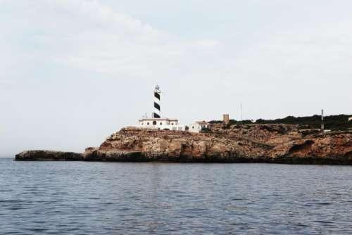 lighthouse coast sea rocks water