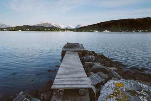 wood dock lake water rocks