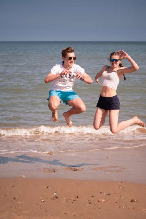people jumping beach boy girl
