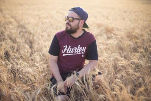 man sitting field sunglasses people