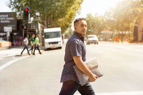 man crossing road business suitcase