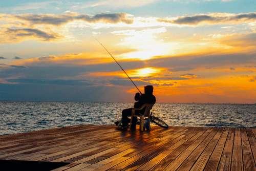 man fishing sunset travel landscape