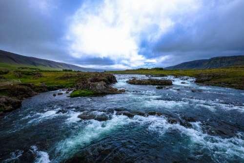 river water rocks green grass