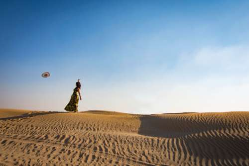 woman throwing hat sand dune