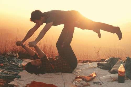 woman lifting man blanket picnic