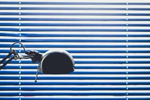 blue blinds lamp desk window