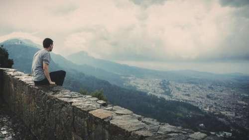 guy looking sitting ledge city