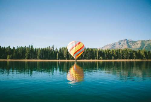 hot air balloon blue sky lake water