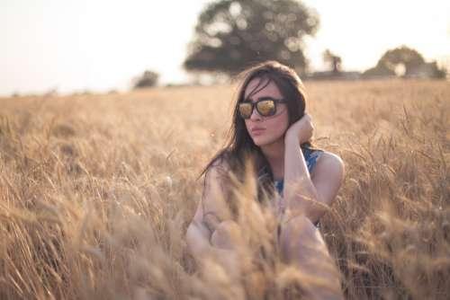 woman sitting field sunglasses reflection