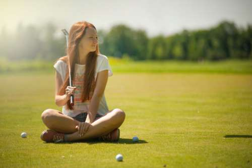 woman cross legged golf course sunny