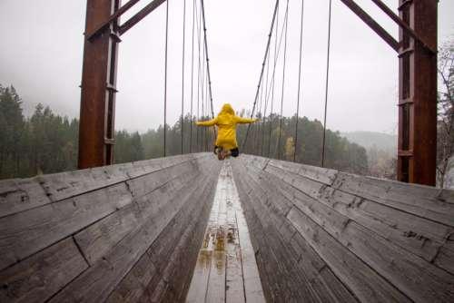 jump rain raincoat bridge trees
