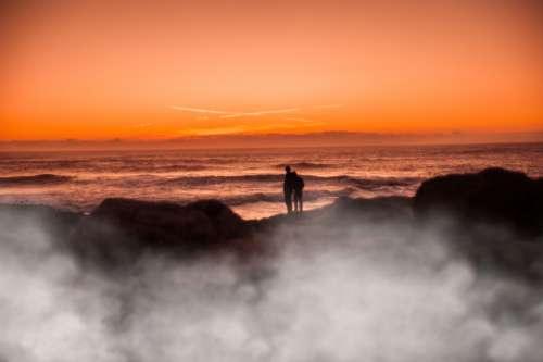 ocean sunset couple people silhouette