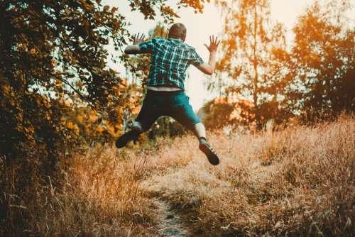 man jumping forest trail walk