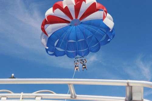 parachute blue sky clouds people