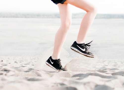 woman sneakers jumping summer beach