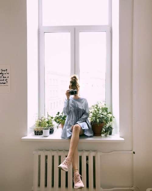 woman crossed legs window sill