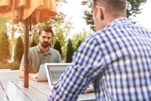 man outside working laptop tablet