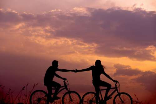 silhouette bike bicycle couple holding hands