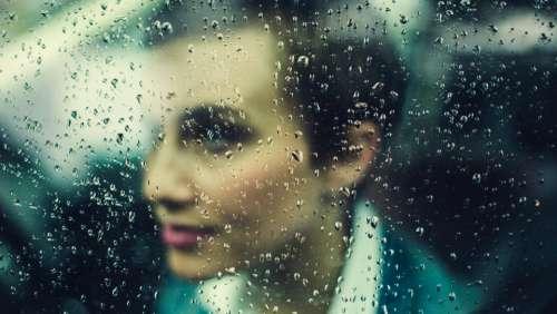 woman rain window wet bokeh