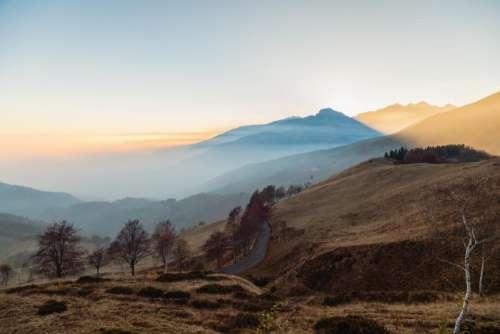 highland mountain grass sky clouds