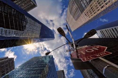 stop sign city skyscraper blue sky