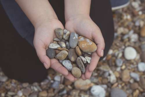 pebbles rocks hands beach
