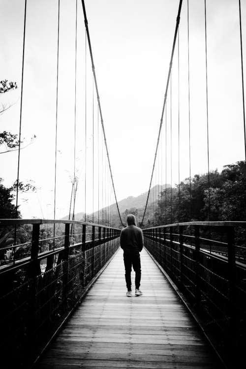 man walking bridge black & white people