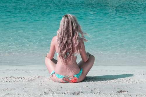 woman yoga beach blue water