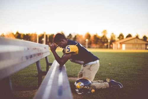 man people kneel praying bench