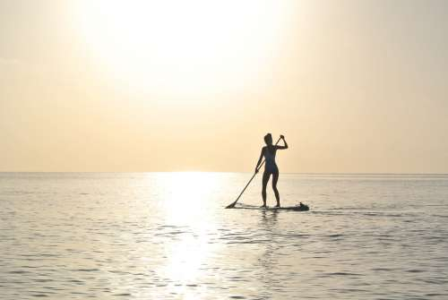 woman paddleboard sunset dusk evening