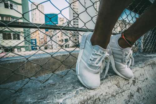 sneakers shoes feet concrete chainlink