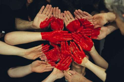 red paint heart palm hands