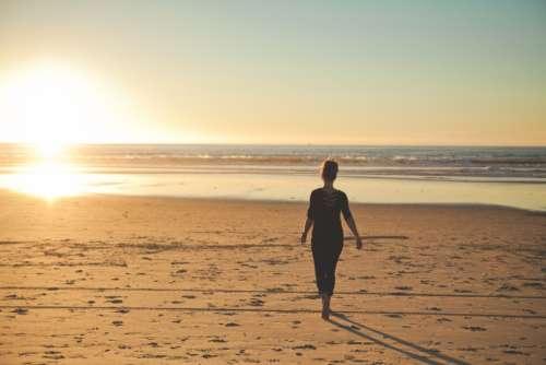 woman beach sunset walk sand