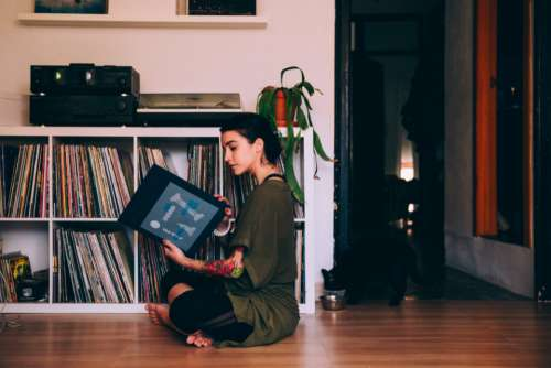woman sitting reading records vinyl