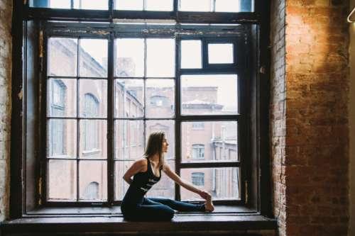 woman stretch window sill city