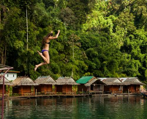 woman jumping water huts sea