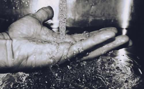 black and white hand fingers running water drop