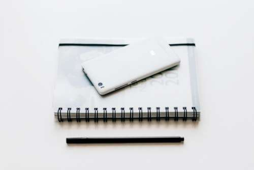 black and white notebook pen mobile phone